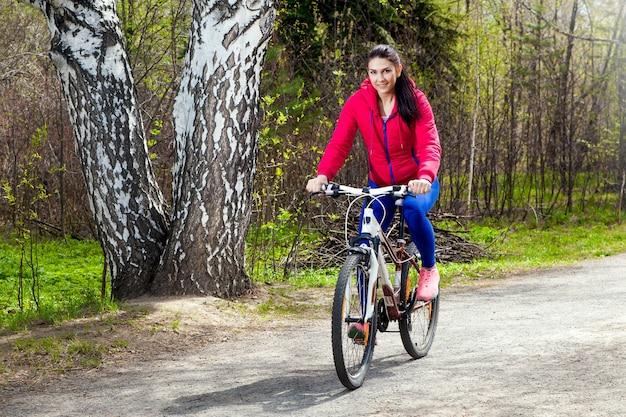 Jeune femme marche dans la forêt de printemps sur un vélo
