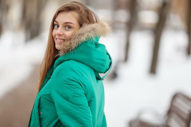 Jeune femme marchent dans le parc d'hiver