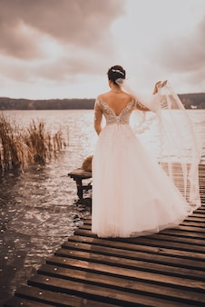 Une jeune femme mariée en robe de mariée blanche cheveux bouclés rouges se dresse sur la jetée en bois brun au milieu du lac bleu azur.