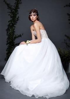 Jeune femme mariée en robe de mariée en studio avec maquillage et coiffure