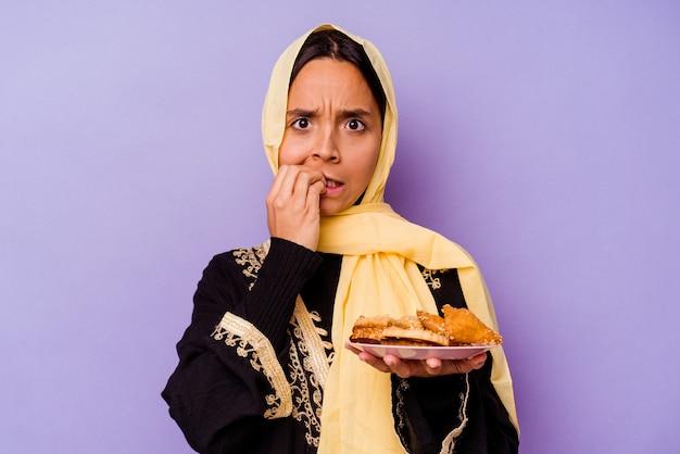 Jeune femme marocaine tenant un bonbon arabe isolé sur fond violet se rongeant les ongles, nerveuse et très anxieuse.