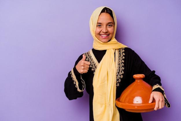 Jeune femme marocaine tenant un tajine isolé sur fond violet souriant et levant le pouce vers le haut