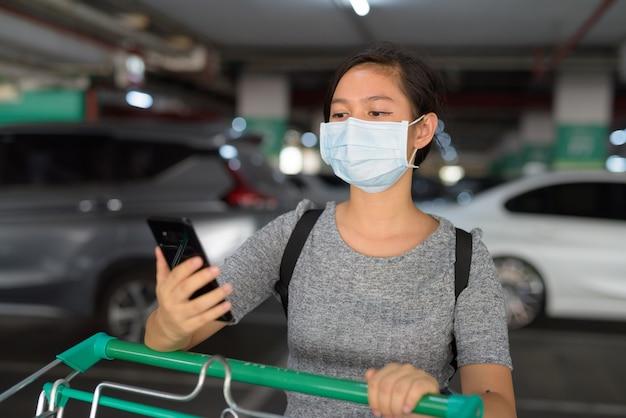 Jeune femme avec masque à l'aide de téléphone tout en tenant le caddie sur le parking