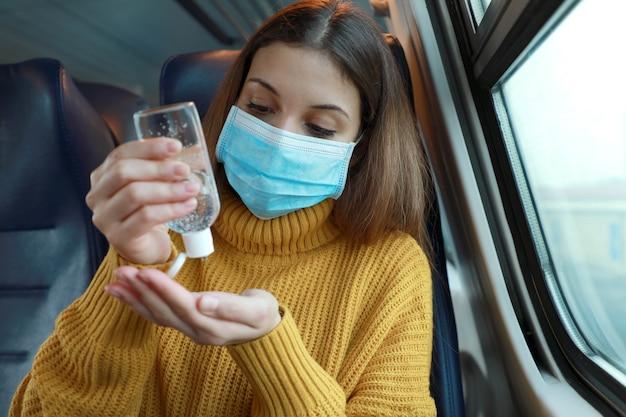 Jeune femme avec masque chirurgical à l'aide de gel désinfectant pour les mains du distributeur