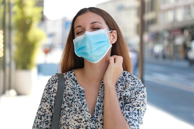 Jeune femme avec masque chirurgical démangeaisons symptômes d'allergie se gratter le cou dans la rue de la ville