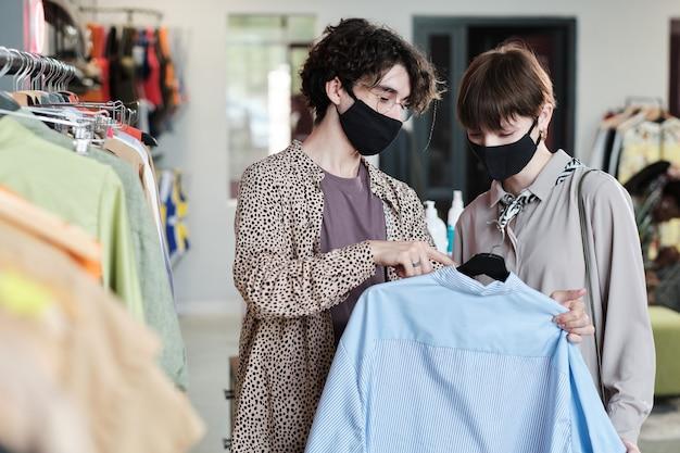 Jeune femme en masque choisissant une nouvelle chemise avec l'aide d'une vendeuse dans le centre commercial