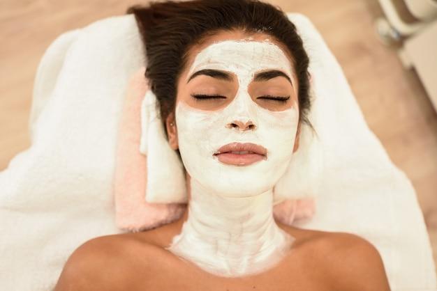 Jeune femme avec un masque de crème hydratante sur son visage
