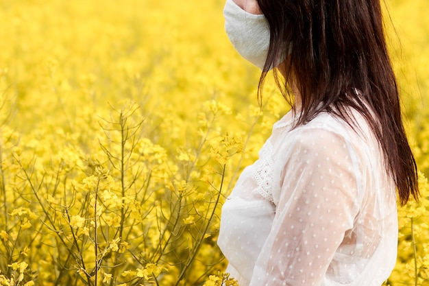Jeune femme avec masque dans un champ avec des fleurs de viol