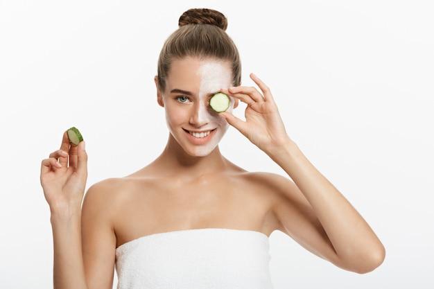 Jeune femme avec un masque facial à l'argile tenant des tranches de concombre isolés sur fond blanc.