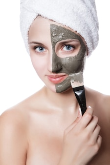 Jeune femme avec masque facial dans un spa de beauté.