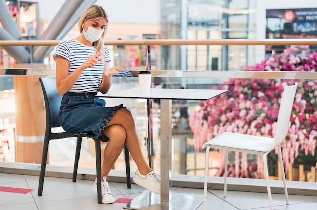 Jeune femme avec masque facial désinfectant les mains