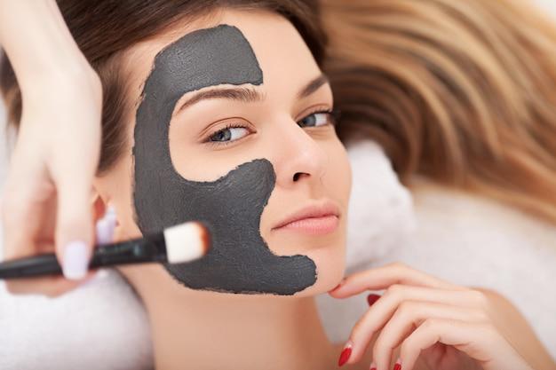 Jeune femme avec un masque facial naturel dans un spa de beauté