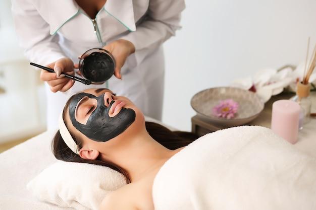 Jeune femme avec masque facial nutritif dans un salon de beauté