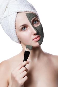 Jeune femme avec masque facial en spa de beauté.