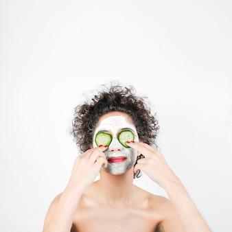 Jeune femme avec masque facial et tranches de concombre sur le visage sur fond blanc