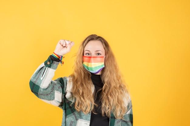 Jeune femme avec masque de fierté gay tenant le symbole du drapeau arc-en-ciel des lgbt