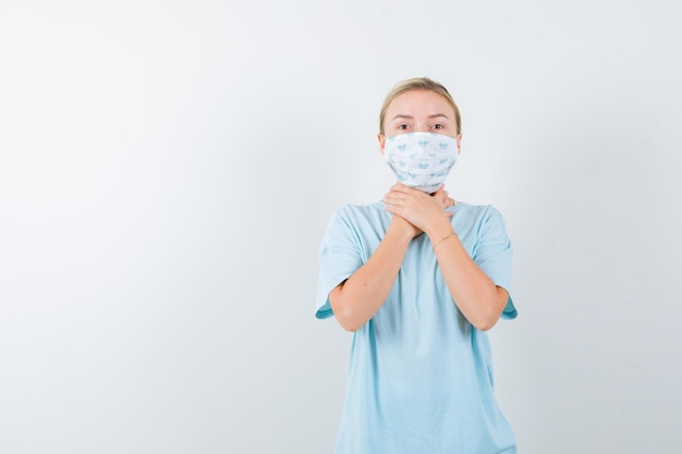 Jeune femme avec un masque médical ayant un mal de gorge