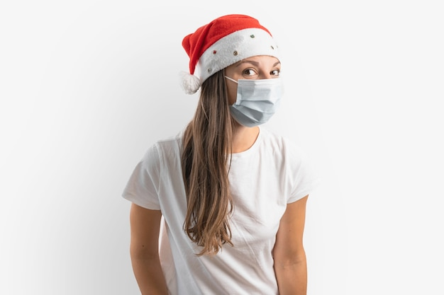 Jeune femme avec masque médical et bonnet de noel sur fond blanc. noël en quarantaine. photo de haute qualité