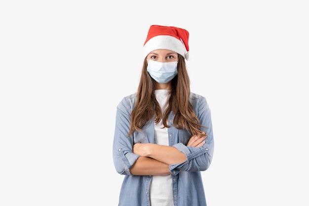 Jeune femme avec masque médical et bonnet de noel sur fond blanc. noël en quarantaine.