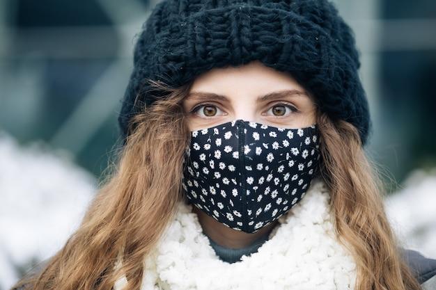 Jeune femme en masque médical debout contre la ville.