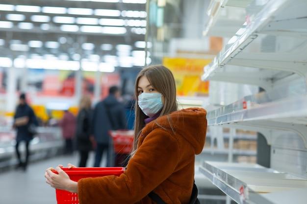 Jeune femme en masque médical et étagères vides en supermarché
