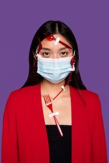 Jeune femme avec masque médical recouvert de vaisselle en plastique