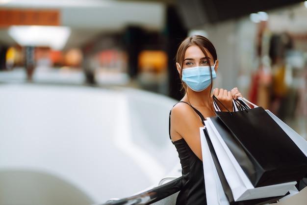Jeune femme en masque médical stérile protecteur sur son visage avec des sacs à provisions dans le centre commercial.