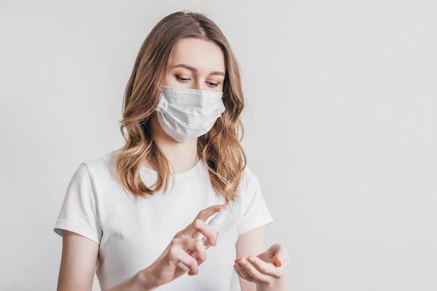 Jeune femme en masque médical, t-shirt blanc se lave les mains avec un spray antiseptique gel