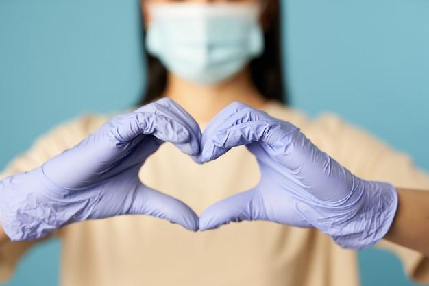 Jeune femme en masque protecteur et gants montrant la forme du coeur avec les mains