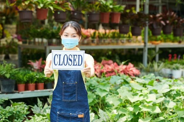 Jeune femme en masque de protection debout dans un centre de jardinage et montrant un panneau fermé