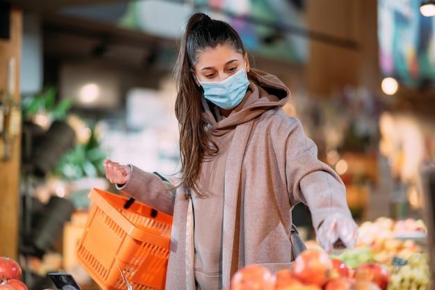 Jeune femme en masque de protection fait des achats