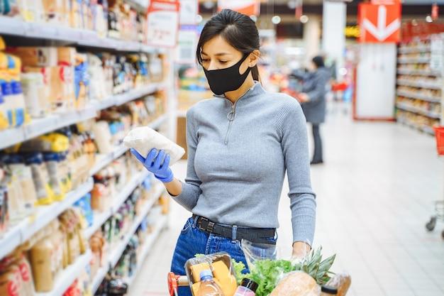 Jeune femme en masque de protection et gants en choisissant des produits dans le supermarché.