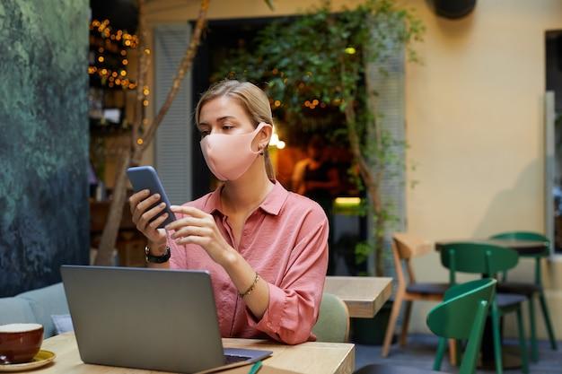 Jeune femme en masque de protection lisant un message au téléphone tout en travaillant à la table avec un ordinateur portable dans un café