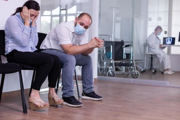 Jeune femme avec masque de protection recevant des nouvelles dévastatrices du médecin sur sa santé, commence à pleurer et se sent perdue, triste, déprimée assise près de son mari dans la salle d'attente d'une nouvelle clinique normale