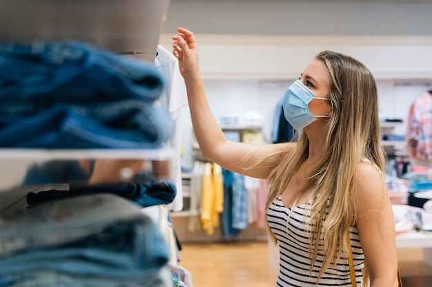 Jeune femme en masque shopping dans un magasin de vêtements dans la pandémie de coronavirus