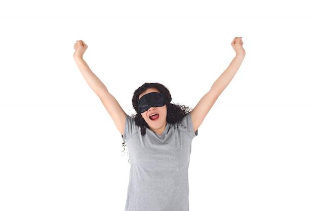 Jeune femme avec masque de sommeil se réveiller et étirer les bras