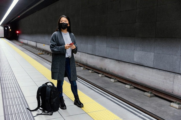 Jeune femme avec masque à la station de métro