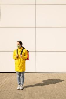 Jeune femme en masque en tissu et manteau jaune debout avec sac thermique à l'extérieur, elle livre de la nourriture pendant la pandémie de coronavirus