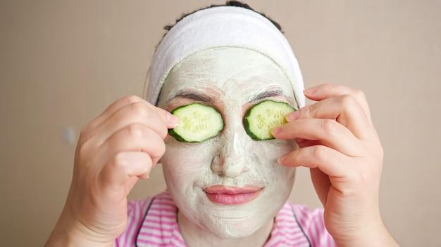 Jeune femme avec masque sur le visage jouant avec des anneaux de concombre, fermant les yeux.