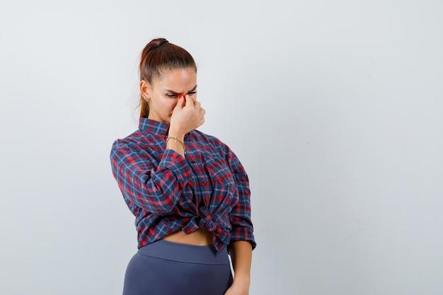 Jeune femme massant le pont nasal en chemise à carreaux, pantalon et à l'air épuisé. vue de face.