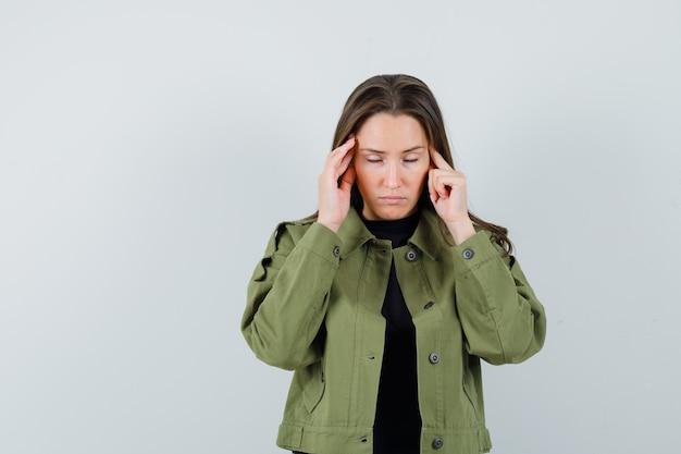Jeune femme massant sa tempe en veste verte, chemise noire et à la vue stressante, de face.