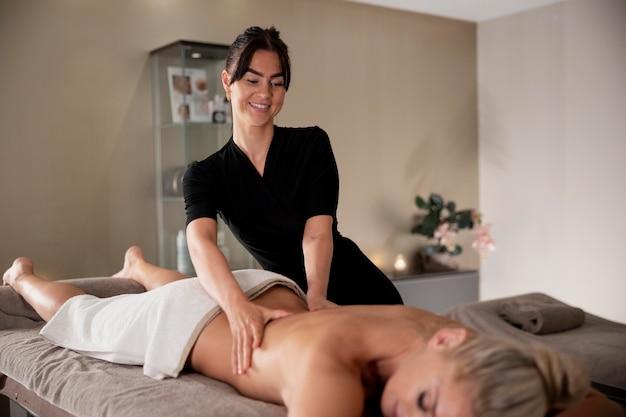 Jeune femme massant son client dans son salon