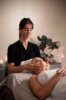 Jeune femme massant le visage de son client