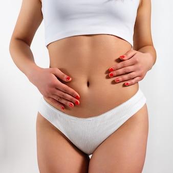 Une jeune femme masse son ventre à deux mains. sur fond blanc. la santé de l'estomac et les bons concepts de digestion. haute résolution