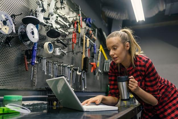 Jeune femme mécanicien avec ordinateur portable
