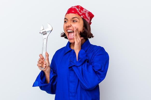 Jeune femme mécanique tenant une clé isolée criant et tenant la paume près de la bouche ouverte.