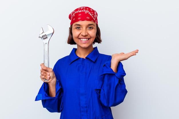 Jeune femme mécanique tenant une clé isolée montrant un espace de copie sur une paume et tenant une autre main sur la taille.
