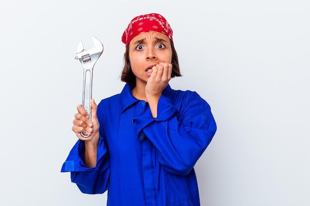 Jeune femme mécanique tenant une clé isolée des ongles mordants, nerveux et très anxieux.