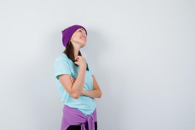 Jeune femme avec des mèches de cheveux, regardant vers le haut en t-shirt bleu, bonnet violet et gaie, vue de face.