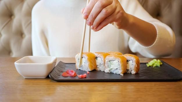 Jeune femme méconnaissable mangeant des rouleaux de saumon assis dans un café.